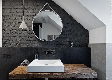 Современное зеркало на фоне кирпичной стенки