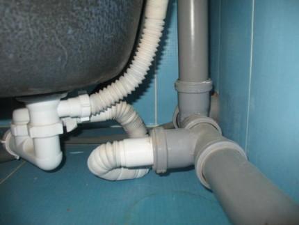 Сифонная система, подключенная к трубам канализации, с помощью гофрированной трубы.